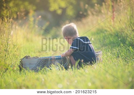 Boy in vintage blue sailor suit playing in wooden boat, pretending to sail across summer sea of grass. Adventure, children activity, game.