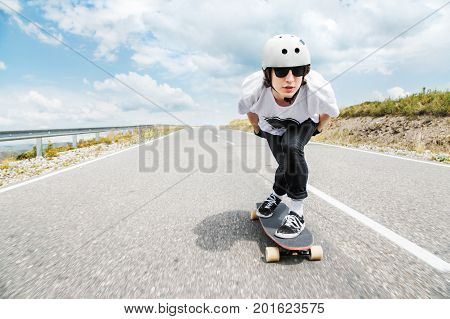 A young guy in helmet and sunglasses rides a country road at high speed in the rain amid thunderstorm clouds