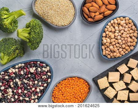 Vegetarian or vegan healthy protein sources concept. Quinoa, chickpea, almond, red lentils, mixed bean, broccoli, tofu on gray concrete background. Close up. Top view or flat lay. Copy space.