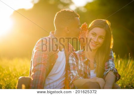 Young man whispering to woman - outdoor in nature at sunset