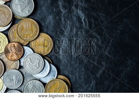 International coins background on black stone table top texture with copy space
