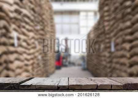 Hemp Sacks Containing Coffee Bean In Warehouse. Stacked Sacks In Storehouse With Wood Table For Disp