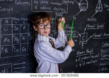 Puzzled schoolboy stands by a blackboard on a chemistry lesson. Educational concept.