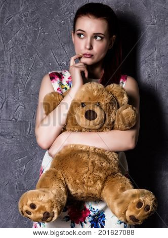 pensive or offended beautiful woman embraces a teddy bear on a gray background