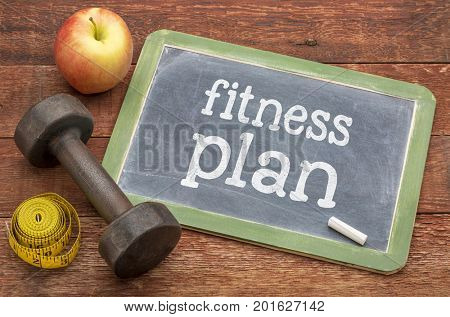 fitness plan concept -  slate blackboard sign against weathered red painted barn wood with a dumbbell, apple and tape measure