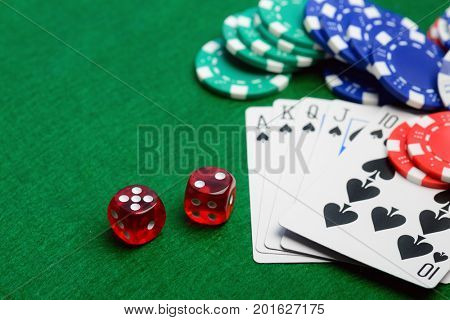 Casino green table with chips, money, play cards and dices. Poker game concept