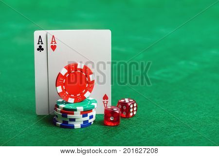 Casino poker chips, dice and cards  on green table background with copy space for your text