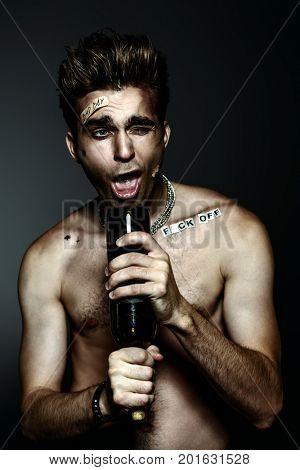 Antisocial behavior, bad habits. Portrait of a bad boy smoking cigarette. Rocker, punk.