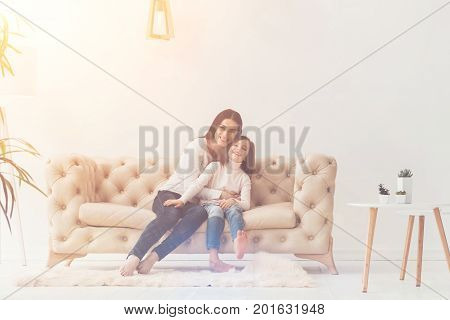 Love you, sweetie. Beautiful loving cheerful mom and daughter showing their feelings while sitting on sofa and hugging each other