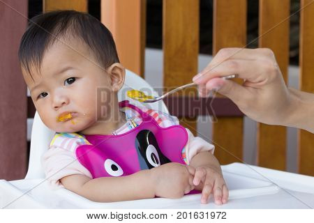 Asian cute baby boring eat food Mother feeding solid food for young kid eight month.