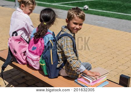 Schoolkids With Books Sitting On Bench