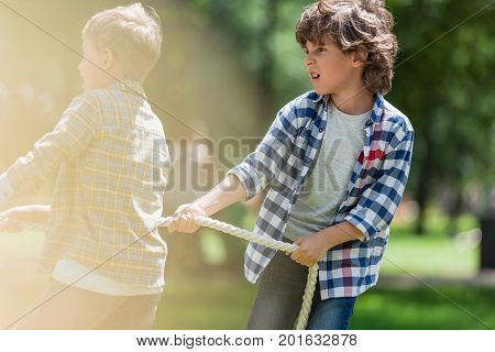 cute little boys playing tug of war together in park