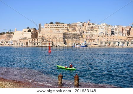 VALLETTA, MALTA - MARCH 31, 2017 - Valletta waterfront buildings including Upper Barrakka Gardens seen from across the Grand Harbour in Vittoriosa with a canoeist in the foreground Valletta Malta Europe, March 31, 2017.