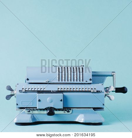 Old Calculating Machine On A Green Background. Accounting Or Business Concept