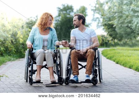 Tender feelings. Nice senior disabled couple sitting in the wheelchairs and resting in the park while expressing love