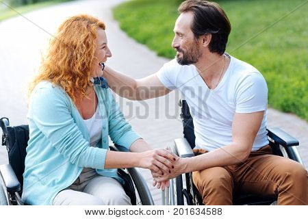 Eternal love. Pleasant senior disabled couple expressing love and sitting in the wheelchairs while resting in the park