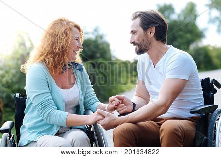 In a good mood. Cheerful pleasant disabled couple sitting in the wheelchairs and resting in the park while having a walk