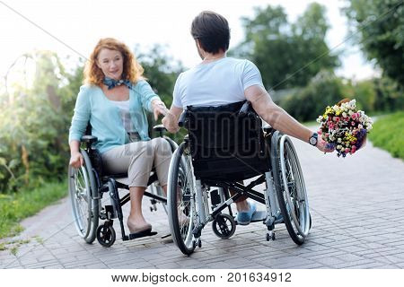 Little surprise. Rear view of a nice pleasant wheelchaired man holding a bunch of flowers behind his back and presenting it to his beautiful wife while resting in the park