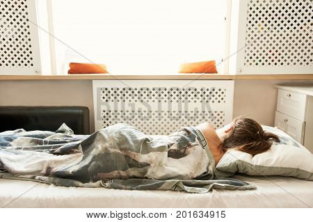Little sleeping girl in her bedroom on bed linen in rays of sunlight. Indoors horizontal closeup filtered image.