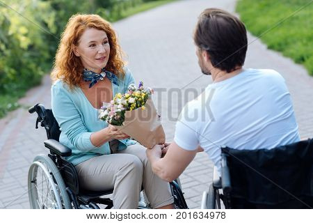 Thank you. Pleasant senior wheelchaired woman getting flowers from her loving husband while having a walk together in the park