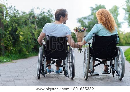 Lets build the future together. Pleasant senior disabled couple sitting in the wheelchairs and holding a bunch of flowers while enjoying leisure time in the park