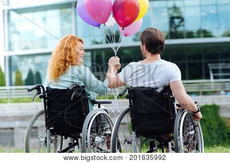 Nice day. Rear view of a senior disabled couple holding balloons and sitting in the wheelchairs and resting outdoors