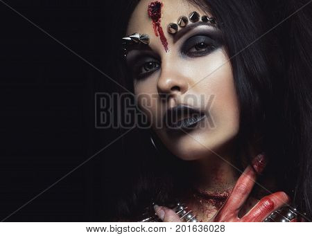 Demon girl with a bullet in the head and her throat cut. An image for Halloween. Photos shot in studio