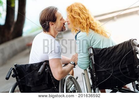 Love me sweet. Pleasant senior disabled couple sitting nose to nose in the wheelchairs and resting in the park while expressing their feelings