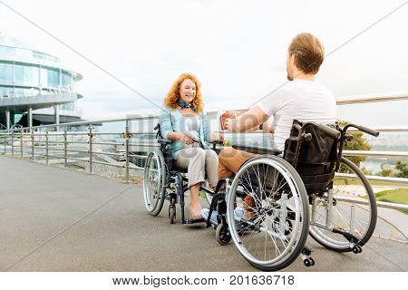 Thats for you. Pleasant disabled man giving a present to a beautiful smiling woman while sitting in the wheelchairs outdoors