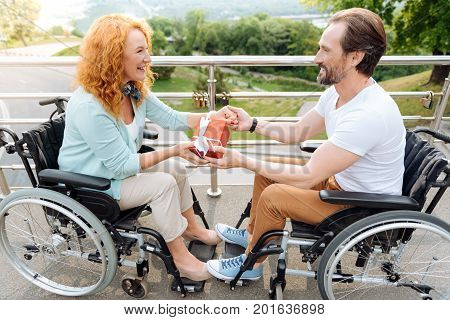 Little aniversary. Positive overjoyed senior couple sitting in the wheelchairs and holding a present while holding hands of each other