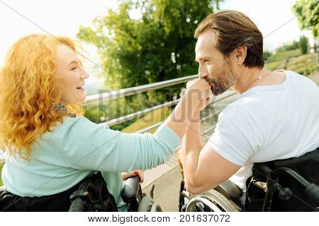 My love. Pleasant handsome senior man in the wheelchair kissing a hand of his loving beautiful disabled wife while having a walk in the park on the weekend
