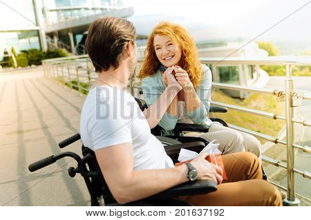 Reveal your love. Positive beautiful disbaled woman holding hand of her loving husband while expressing love and resting outdoors
