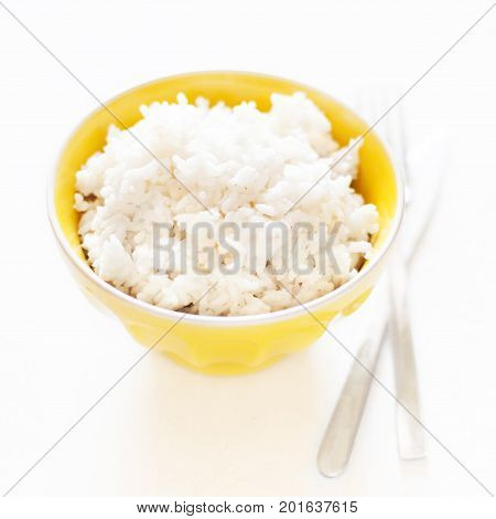 White cooked rice in a yellow bowl over white background close up