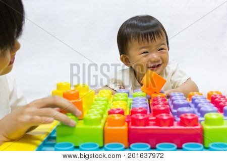 Asian adorable baby one year is playing jigsaw toy for kid support interested with mother parent. Activities family to enhance learning development.