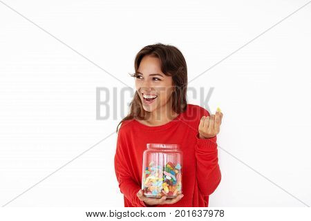 Attractive joyful young Latin female wearing red sweater smiling broadly enjoying sweets out of glass jar. Pretty girl eating candies or jelly beans after dinner having relaxed and cheerful look