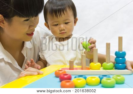 Asian adorable baby one year is playing color puzzle pyramid for kid support interested with mother parent. Activities family to enhance learning development.