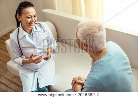 Feeling comfortable. Positive nice friendly nurse sitting on the sofa and talking to her patient while asking him about his health