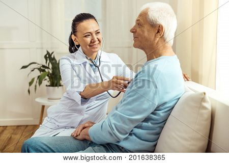 Caring about health. Professional nice female nurse wearing a stethoscope and doing the auscultation while examining her elderly patient