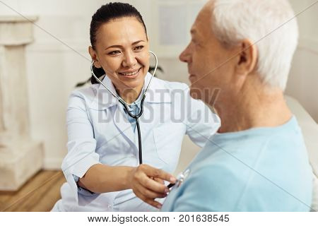 Staying healthy. Professional happy female doctor wearing a stethoscope and smiling while auscultating her aged patient