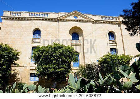 VITTORIOSA, MALTA - MARCH 31, 2017 - View of the side of the Malta maritime museum with prickly pear cactus in the foreground Vittoriosa Malta Europe, March 31, 2017.