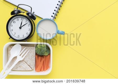 Healthy lunch box on yellow background food clock time concept