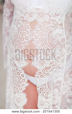 Pregnant woman in white lingerie. Vertical shot with breast