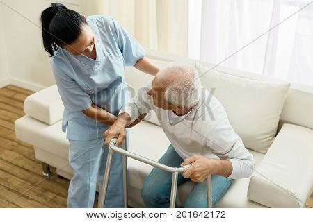 Caring about people. Pleasant delighted friendly caregiver holding her elderly patient and helping him to stand up while doing her job