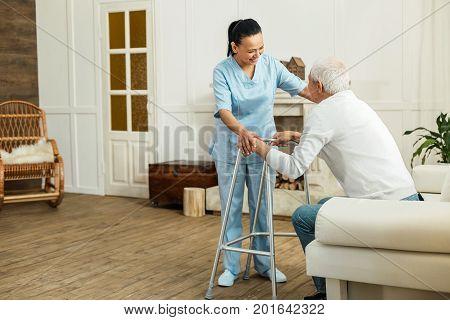 I will help you. Joyful delighted professional caregiver smiling to her patient and helping him to get up while doing her job