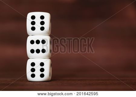 Three white plastic dices on each other on brown wooden board background. Six sides cube with black dots. Devil's number 666.