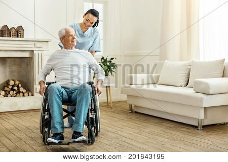 Time for a walk. Cheerful positive female caregiver standing behind her patient and moving a wheelchair while taking him for a walk