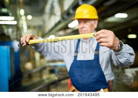 Portrait of senior man unrolling reel tape while working in modern factory workshop