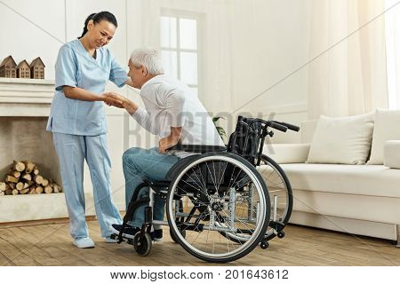 Be slow. Joyful nice helpful caregiver holding her patients hand and looking at him while helping him to get out of the wheelchair