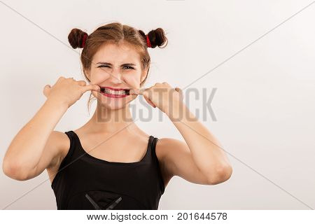 fun beautiful woman grimacing shows her teeth on white background with copy space