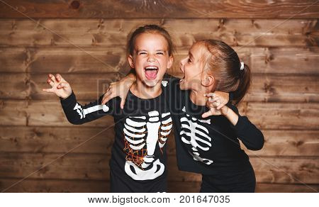 holiday halloween. funny funny sisters twins children in carnival costumes skeleton on a wooden background
